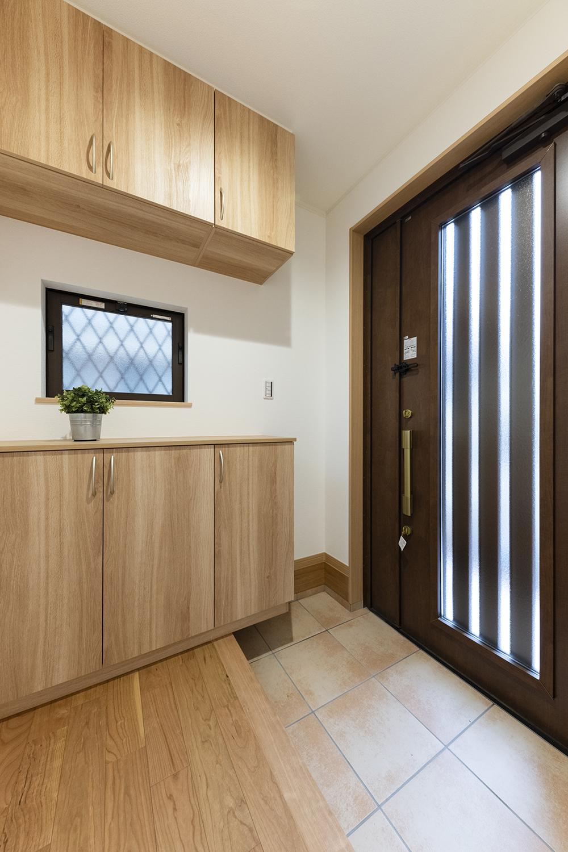 木の温もりを感じるナチュラルな配色の玄関。小窓と玄関ドアの縦スリットから自然の光が差し込む明るい空間。