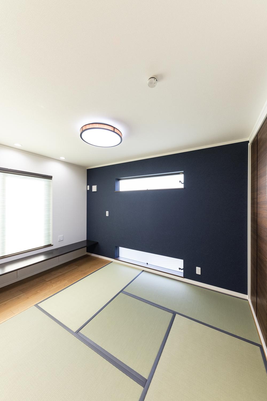 1階畳敷き洋室/濃紺のアクセントクロスや、上下に並べた横窓がモダンな和空間を演出。