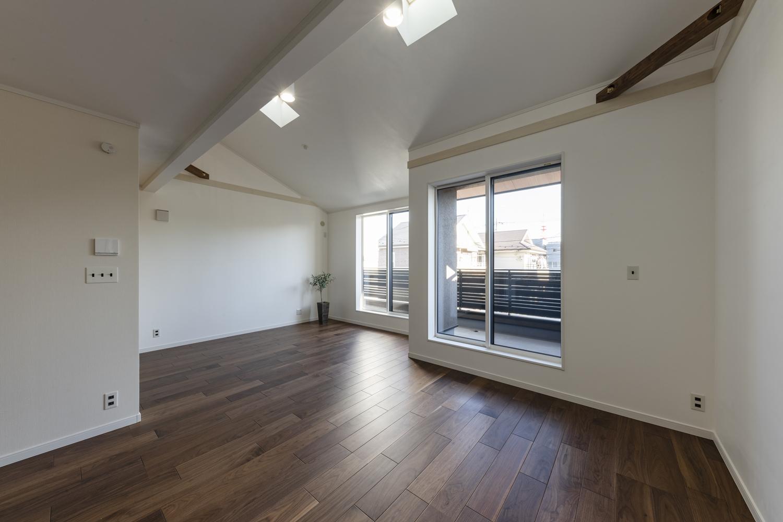 窓から差し込む陽射しが、壁の白さとブラックウォルナットのフローリングのコントラストを鮮やかに引き立てています。