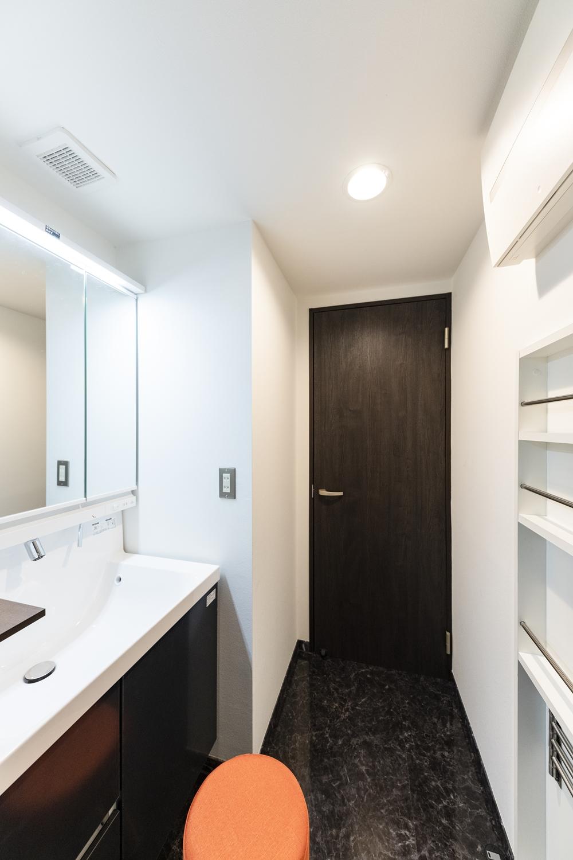 洗面室/洗面化粧台・照明の交換、クロスの貼り替え、床材の上張りを行い、白と黒をベースにしたホテルライクな空間に仕上がりました。