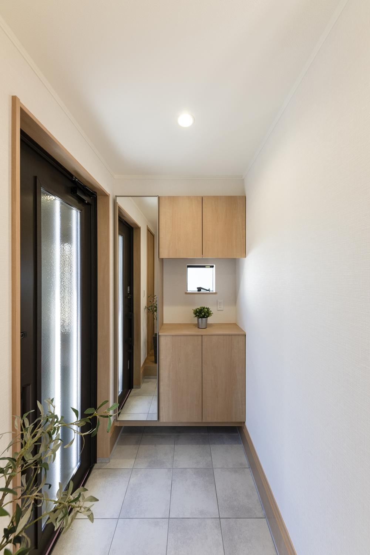 玄関ドアの縦スリットと窓から自然の光が差し込む明るい玄関。