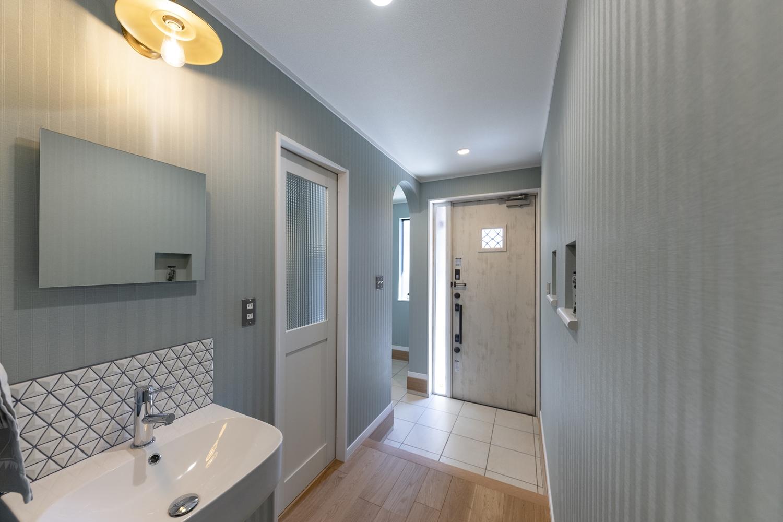 ブルーグリーンの壁紙に白いドアや白いタイルでアクセント。爽やかさと温かみを合わせ持った魅力的な空間。