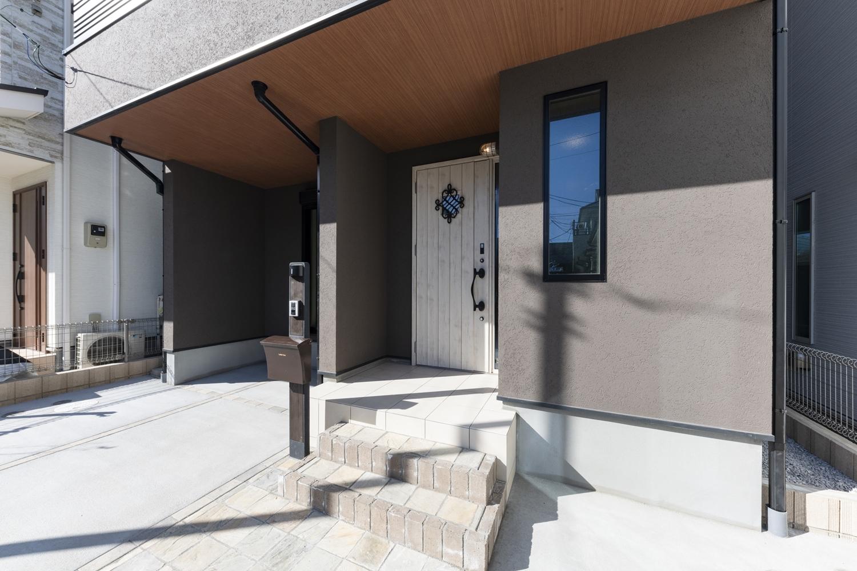 窓に鋳物飾りをあしらった白い玄関ドアがシックな色の外観にアクセントを添えています。軒天に木目調をあしらい、モダンなデザインに。
