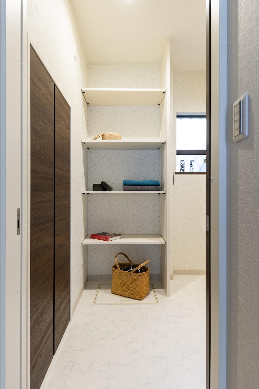 タオルや洗剤等をたっぷり収納できる可動式のリネン棚を設置した脱衣室。
