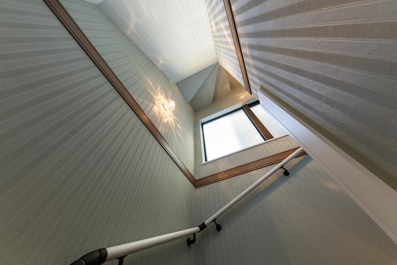 階段/ゆらめく水面をイメージしたブラケットライトが、温かみのある光とキラキラとした陰影が幻想的な空間を演出。