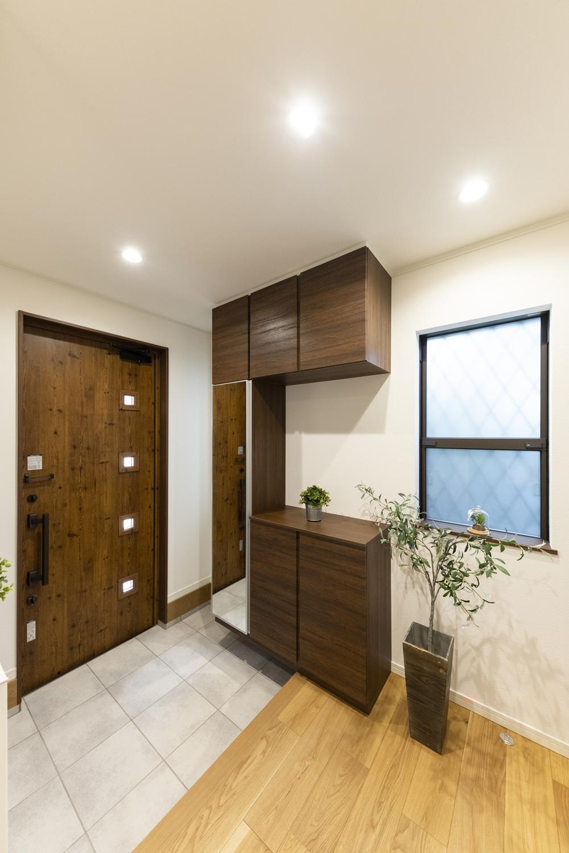 木の温もり感じるナチュラルテイストな玄関。小窓をあしらった可愛らしいデザインのドアを施しました。