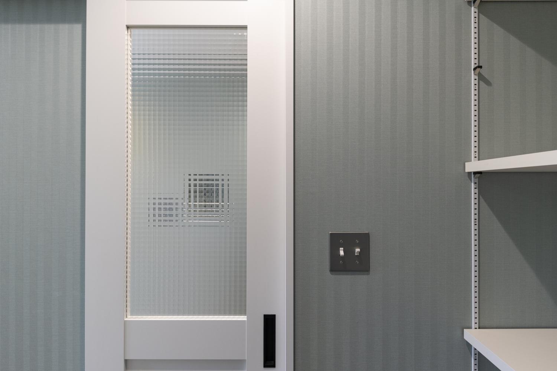 ブルーグリーンの壁紙に白いドアや白いキャビネットでアクセント。爽やかさと温かみを合わせ持った魅力的な空間。