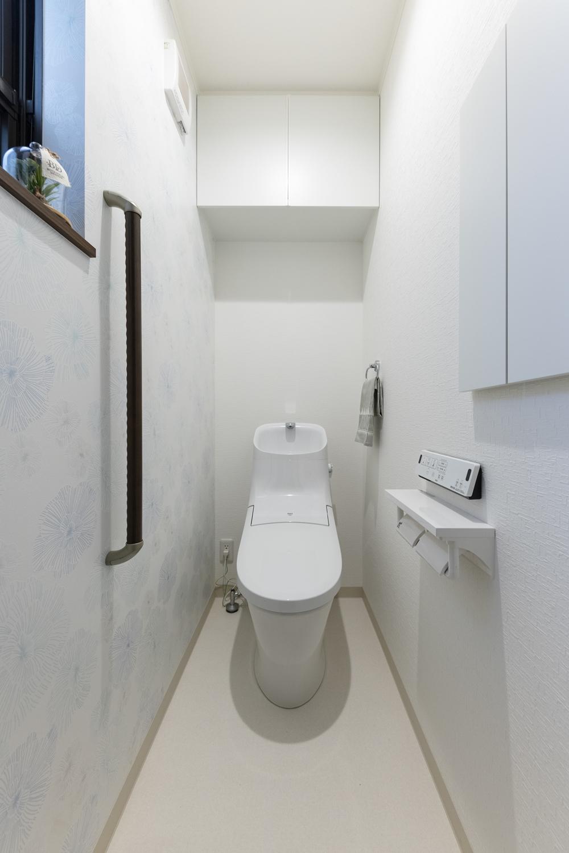 1階トイレ/花柄白いクロスが、さり気なくエレガントに清潔感を演出。手すを設置して安全で快適な暮らしをサポート。