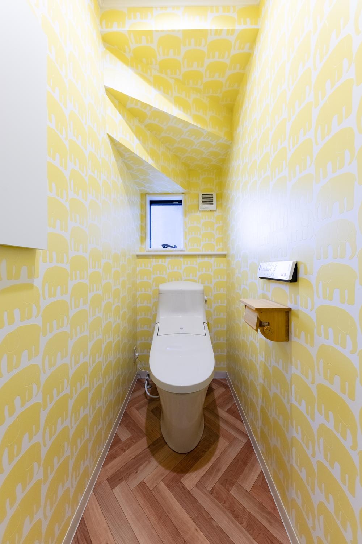 1階トイレ/黄色いアニマルデザインのクロスや、ヘンリーボーン柄のフロアを施したポップで明るい空間。
