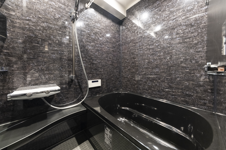 バスルーム/全面改修工事を行いました。ブラックのバスタブや天然石の豊かな表情をモチーフにしたデザインの壁が、上質な空間を演出。