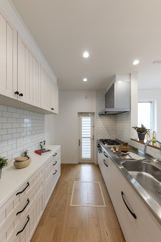 アンティーク感漂う白いキッチン。柔らかなパイン材の扉と、ヨーロッパ製のアンティーク仕上げの取手が、キッチン全体を演出します。