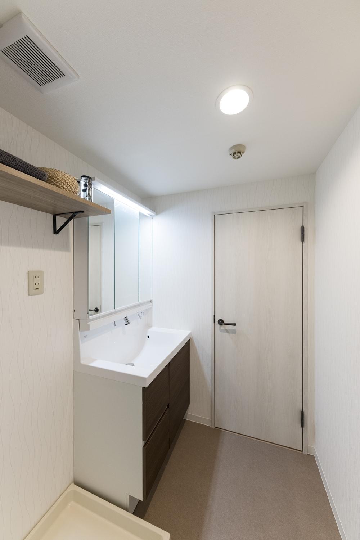洗面室/洗面化粧台・照明の交換、クロス、床材の貼り替えを行いました。白を基調とした清潔感のある空間になりました。