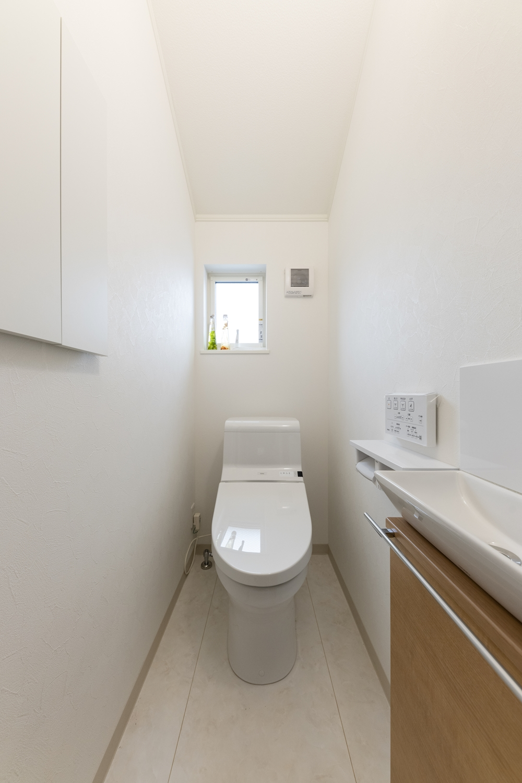 白を基調とした清潔感のある1階トイレ。手洗いや場所をとらないキャビネットを設置して機能的でスッキリとした空間に。