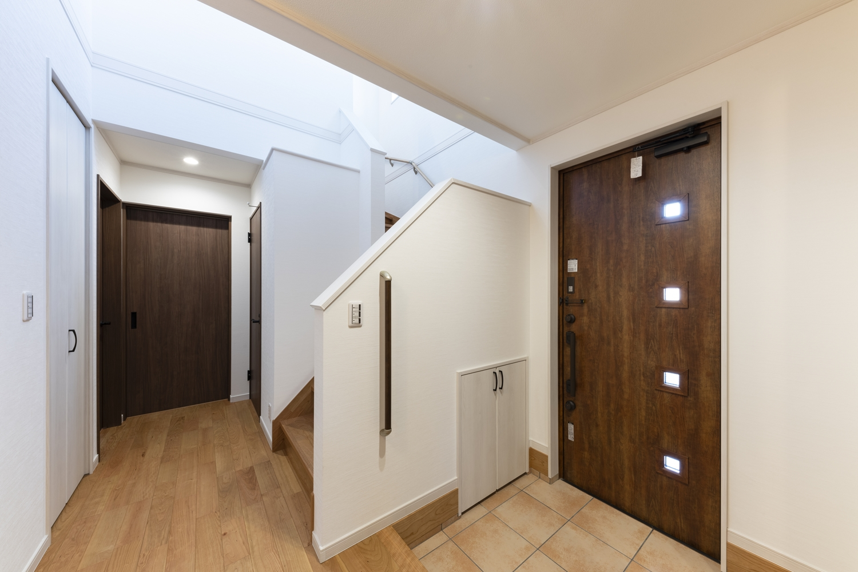 吹抜けから自然のやさしい光が降り注ぐ明る広々とした玄関。昇り降りをやさしくサポートする手摺を設置しました。