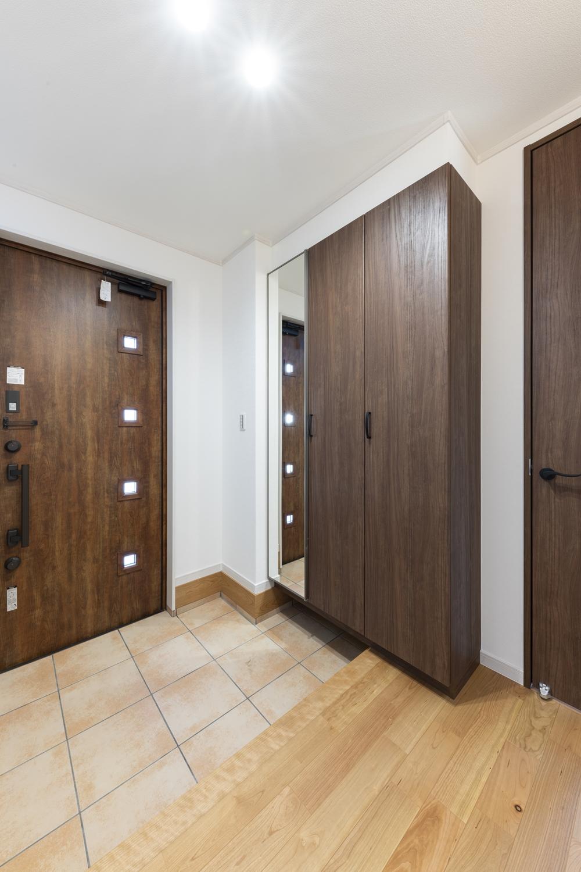 木の温もり感じる玄関ドアや収納、ベージュのテラコッタ調タイルが穏やかな空間を演出。