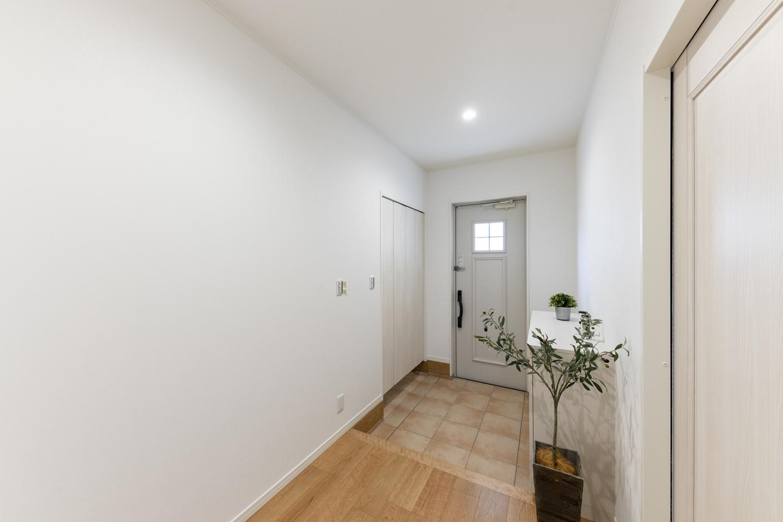 白を基調とした明るくナチュラルな雰囲気の玄関。小窓をあしらった可愛らしいデザインの玄関ドアを施しました。