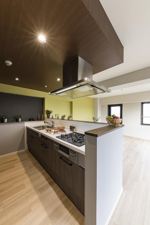 キッチンを対面にする為に、上部の天井を下げて、電気設備関係を通しました。ダークトーンの木目調のクロスやダウンライトを施すことで、グッとおしゃれな空間に仕上がりました♪