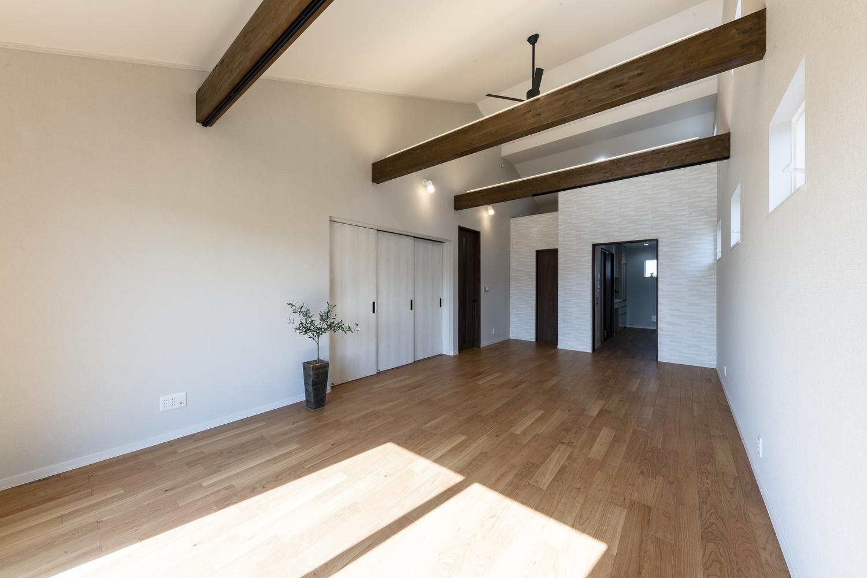 屋根の形に合わせて傾斜を持たせた勾配天井の開放的なリビング。化粧梁がナチュラルな空間を創り出します。