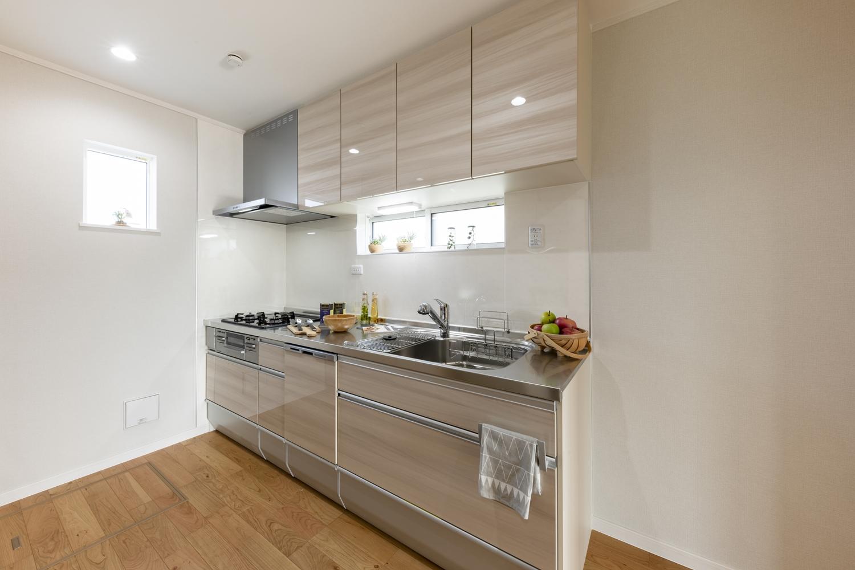 優しい木目調のキッチン扉がやわらかな雰囲気をつくります。窓を設置し採光を確保することで明るいキッチンに。