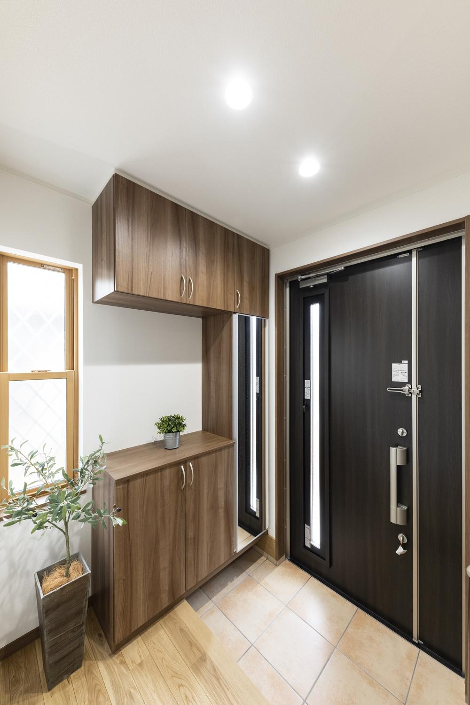 親子扉で、広々玄関。木目調の収納扉でナチュラルな雰囲気に。