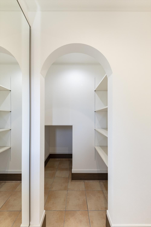 玄関/アーチ状の下がり壁をくぐると便利な土間収納。ベビーカーもウォークイン。