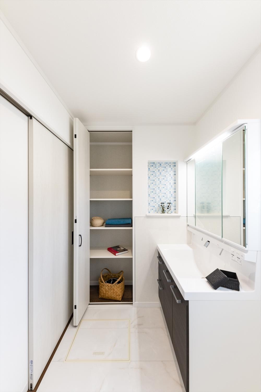 清潔感のある真っ白な空間。タオルや洗剤等をたっぷり収納できる可動式のリネン棚。