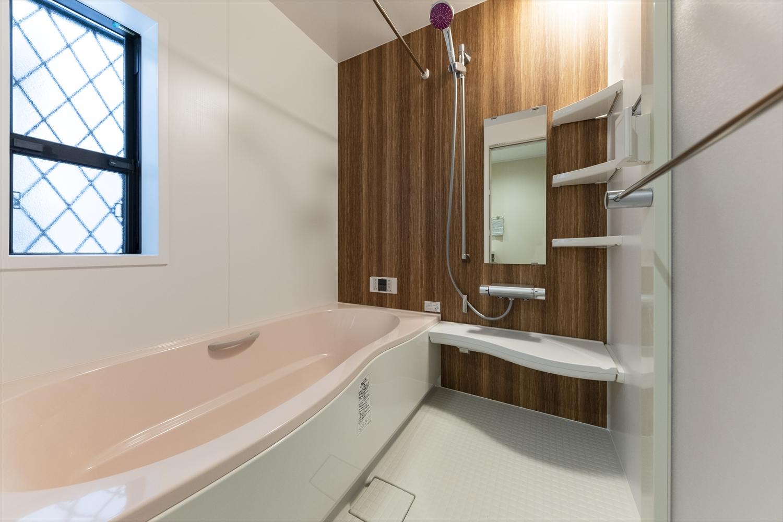木目柄のアクセントパネルと淡いピンクの浴槽が癒しと温かみをプラスし、より安らぎを感じる空間に。
