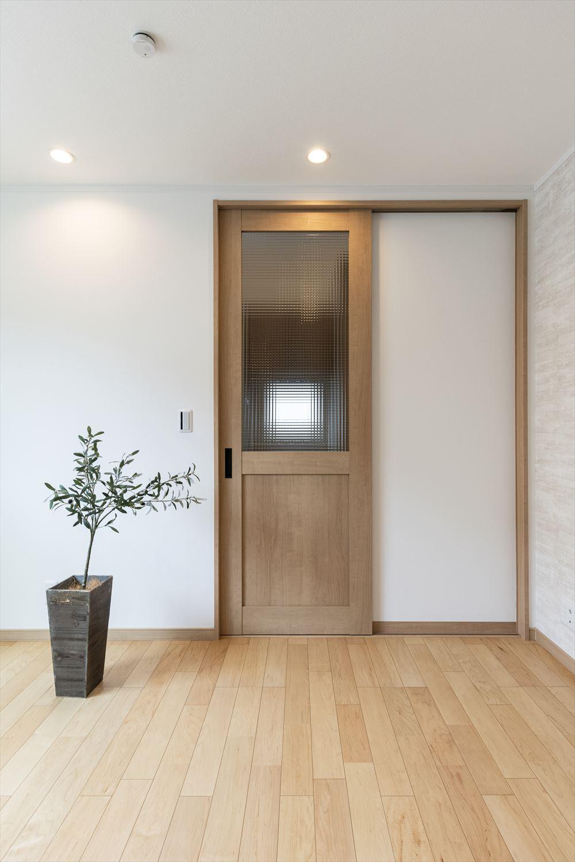 チェッカーガラスが素朴な印象を与えるナチュラルなリビングドア。