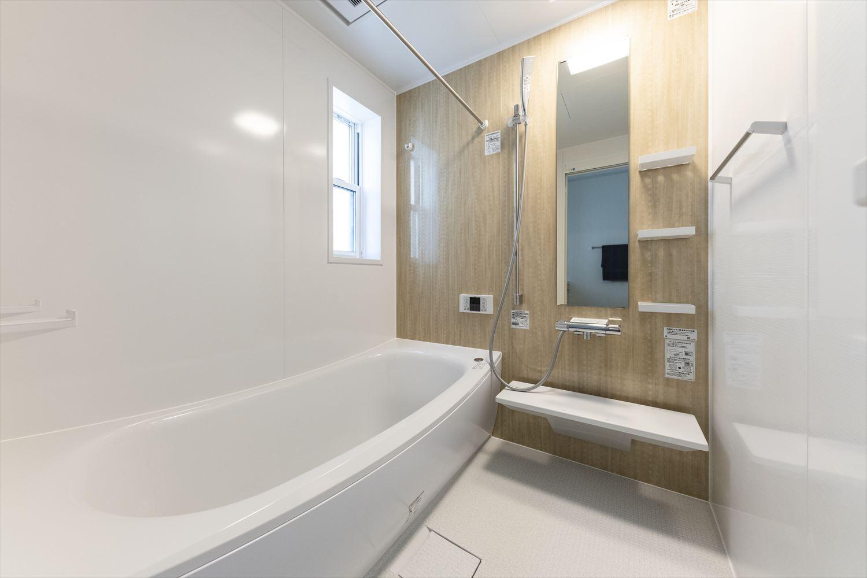 ナチュラルなタルシアエージュのアクセントパネルを使用した、心地良い穏やかな浴室。