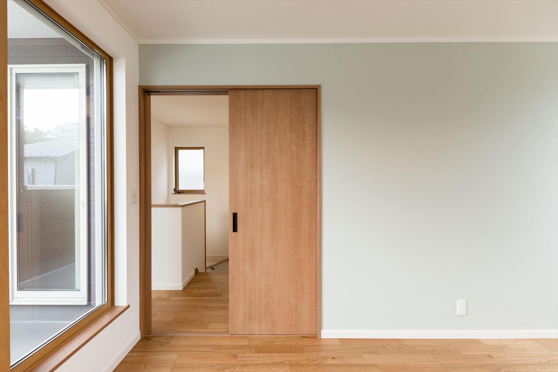 窓から自然のやさしい光が降り注ぐ明るい2階洋室。スペースのムダをつくらない引き戸を採用。