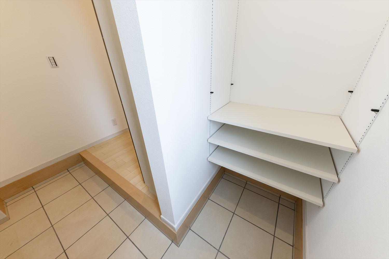 ミラー付きシューズクローク、玄関土間に可動棚を設え収納にゆとりのある玄関スペース。
