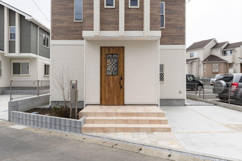 目を引くテラコッタ調玄関タイルとアイアンの装飾が施されたの木製ドア。