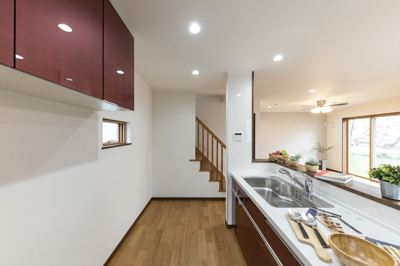 キッチン背面に同じ配色の吊戸棚を設置し、見た目の統一感と使い勝手を良く