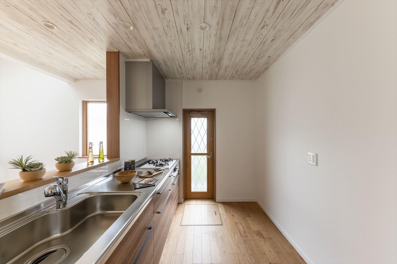 木目のキッチンパネルが空間をよりナチュラルな雰囲気に。