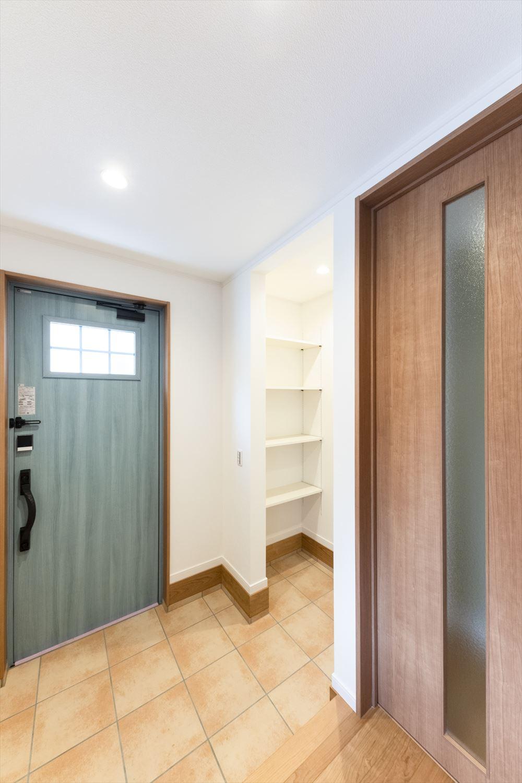 アイスブルーの玄関ドアに、ベージュのテラコッタ調タイルを施した鮮やかな玄関。