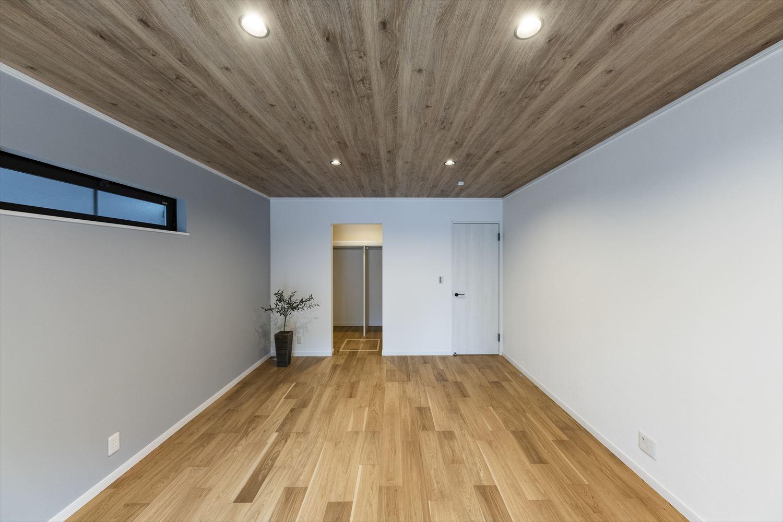 1階洋室/床下収納付のウォークインクローゼットを設えた一室。アクセントクロスと木目の天井が印象的な落ち着きのある空間。