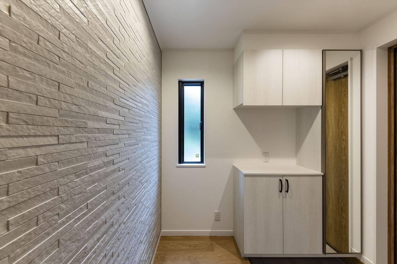 石積み調の壁パネルが印象的なエントランス空間。