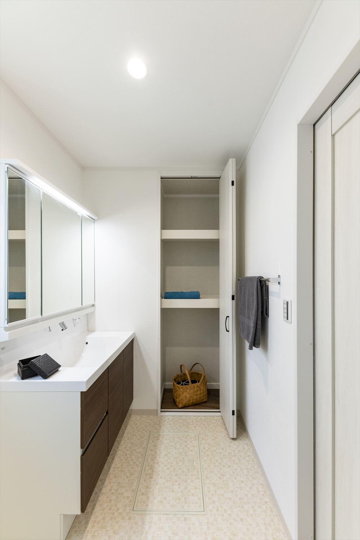 白を基調とした清潔感のあるサニタリールーム。タオルや洗剤等をたっぷり収納できるリネン棚や床下収納を設置し、すっきりとした空間に。