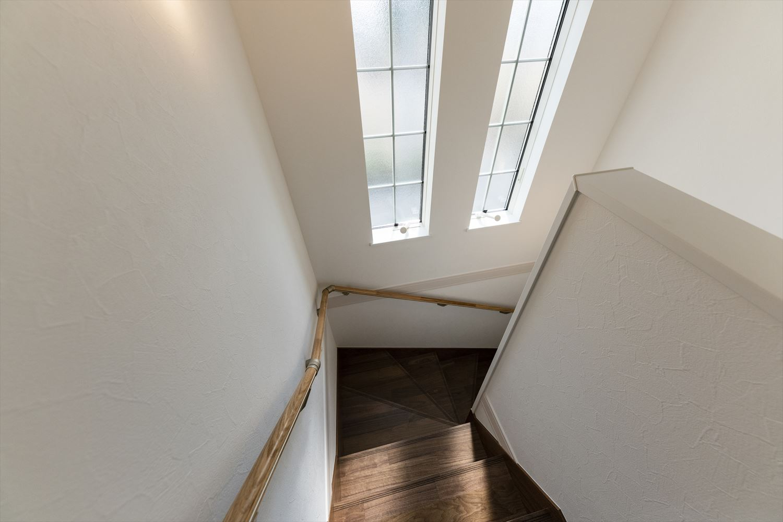 窓からの優しい光が差し込む明るい階段。格子入りの窓が印象的です。