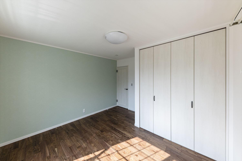 2階洋室/淡いグリーンのアクセントクロスが印象的な室内。
