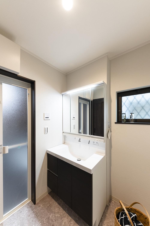 洗面化粧台扉や建具にダークブラウンのアクセントを加えたサニタリールーム。