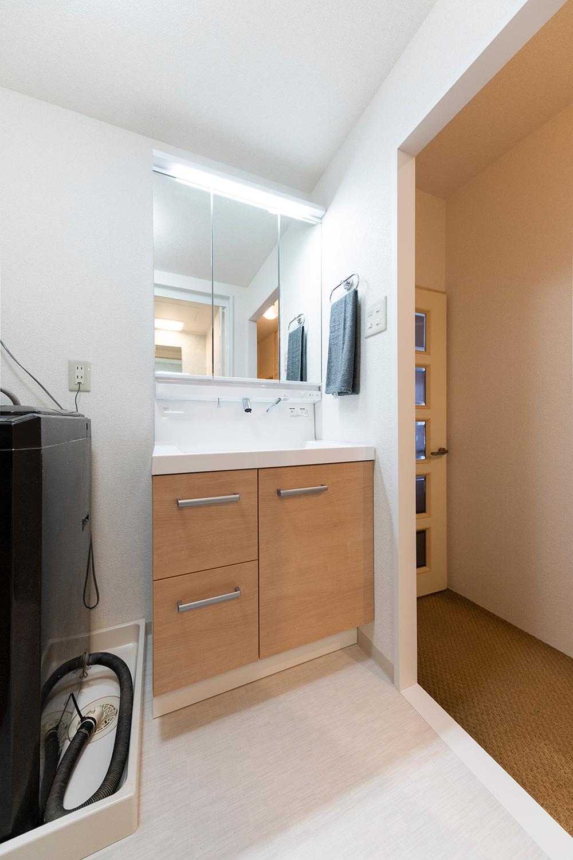 After:浴室をサイズアップしたため、洗面脱衣室は工事前より縮小となりました。脱衣スペースは以前と変わらずお使いいただけるよう奥行50センチと浅めの洗面化粧台を選びました。