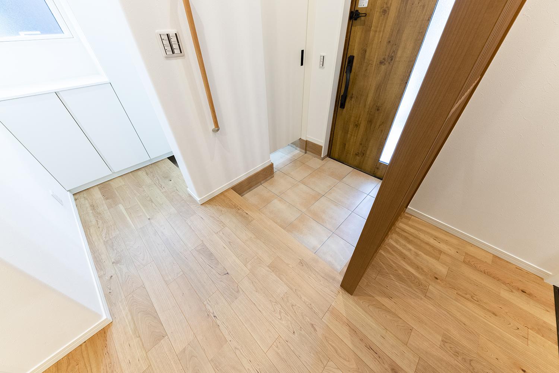 木目のドアやテラコッタ調タイルでナチュラルな雰囲気の玄関スペース。