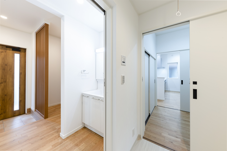 洗面コーナー、脱衣所。奥はパントリー、キッチンと行き止まりなく通れる回遊動線。