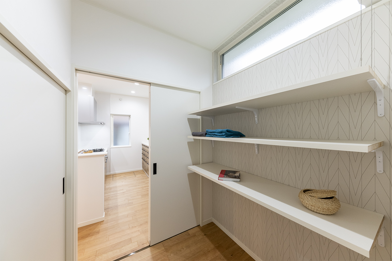 1階パントリー/リビングと洗面所の両方から行き来することができる便利な動線。2帖もの広々したスペースで食品も日用品もまとめて置ける便利なスペース