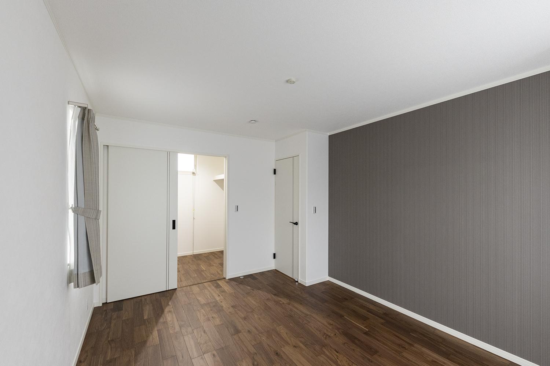 2階主寝室/ブラウンのアクセントクロスとブラックウォルナットの床色がシックに演出された落ち着きのある空間。