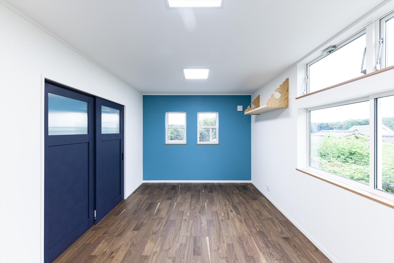 落ち着きのある木目と鮮やかなターコイズブルーの組み合わせでシックに演出された室内