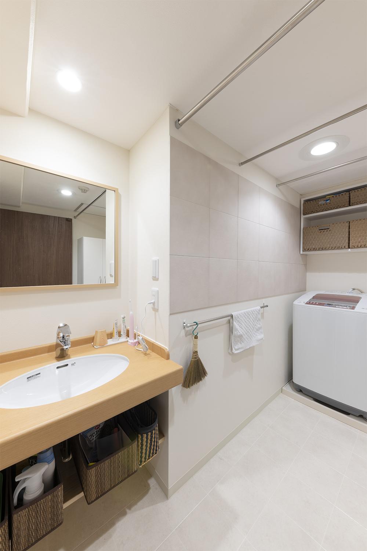 人気のオーダーカウンターのシンプルな洗面台。オープンタイプの収納棚や、湿気と臭い対策にエコカラットタイルを壁に設え使いやすく快適な空間になりました。